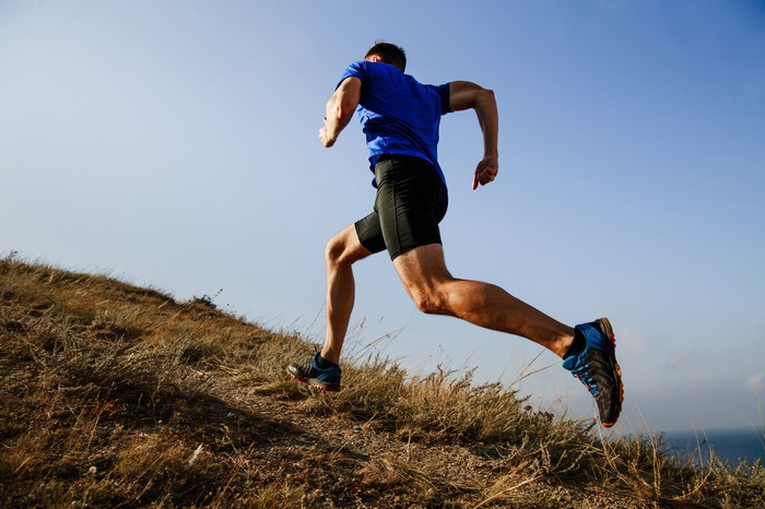 A man running uphill on a trail outside