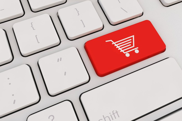 Cutaway of white keyboard with shopping cart icon on red button