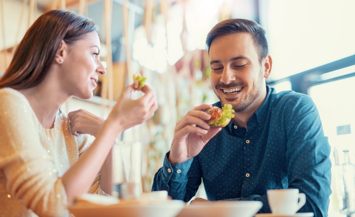 A man and a woman eating sandwiches