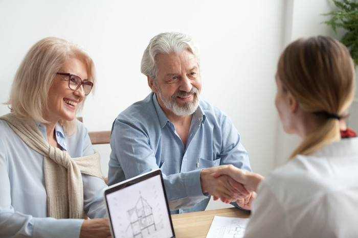 A mature couple shake hands with a financial planner.