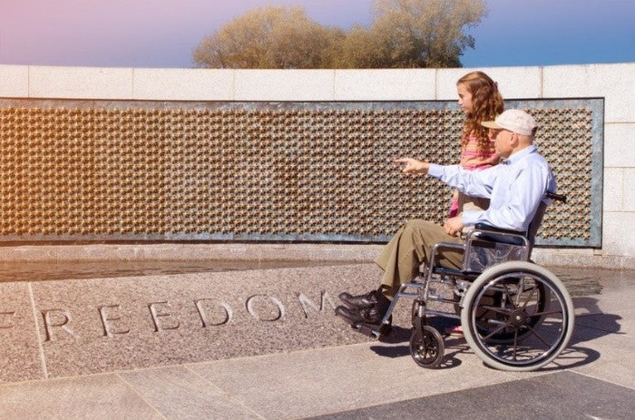 An elderly person using a wheelchair points a companion to a monument reading FREEDOM.