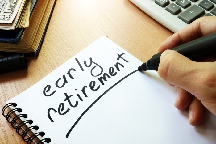 """Money and calculator next to notebook page with """"early retirement"""" written on it"""