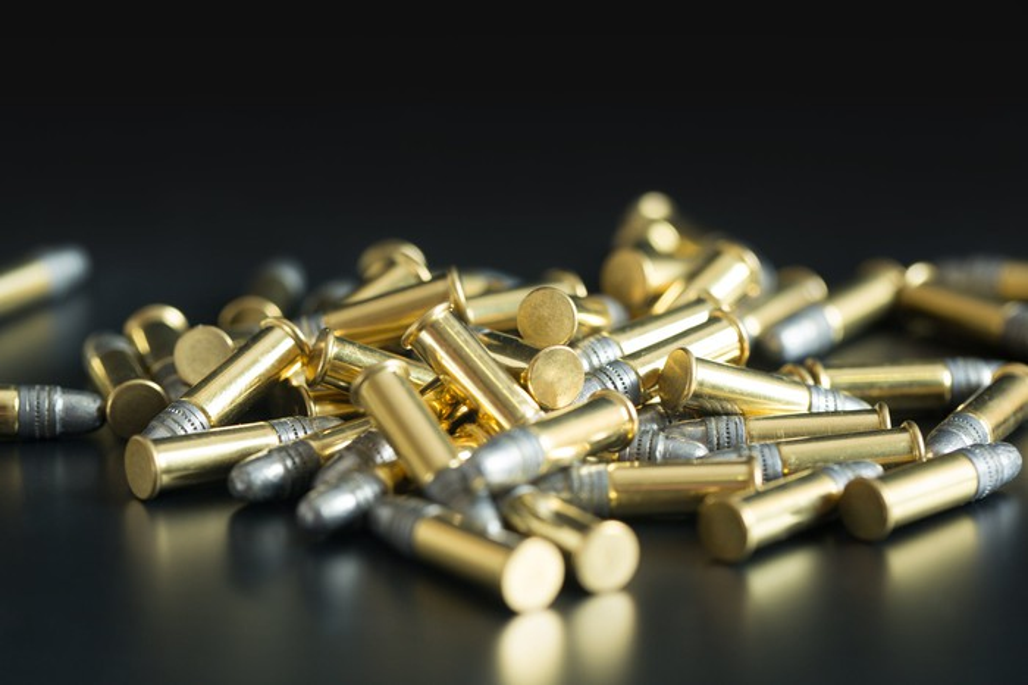 Pile of .22-caliber bullets on black background