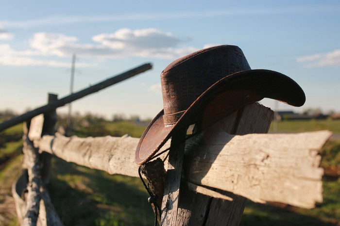 A cowboy hat hanging on a fence post