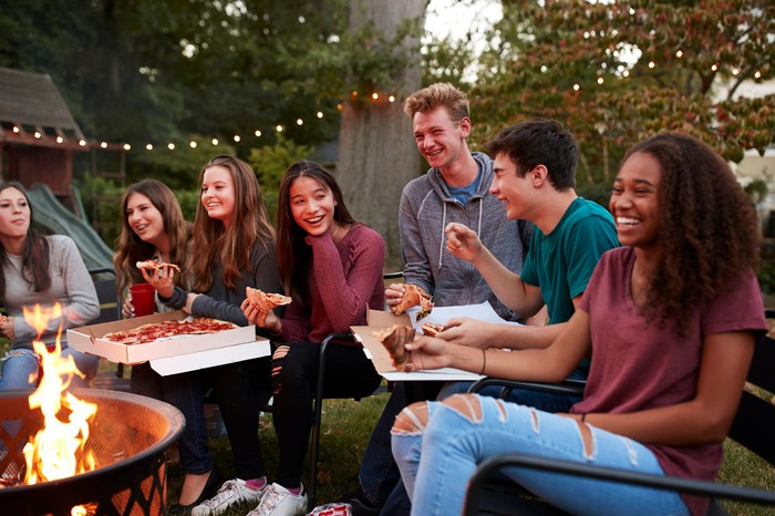 Seven teenagers gathered around a fire pit while eating delivery pizza