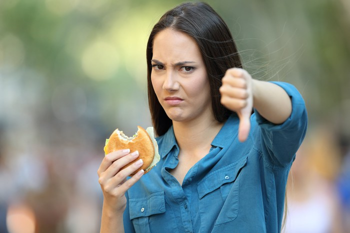 Girl holding a hamburger in one hand and giving a thumbs down with her other hand.