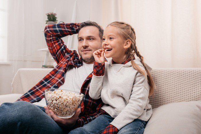 A father and daughter watching TV on the couch with popcorn