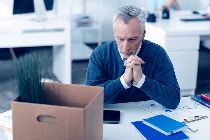 Older man sitting pensively at work, with a cardboard box on his desk