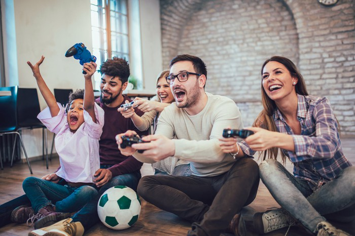 A family excitedly playing video games in the living room