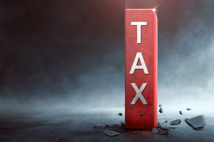 The word TAX written on a large red pole that's bursting through the ground.