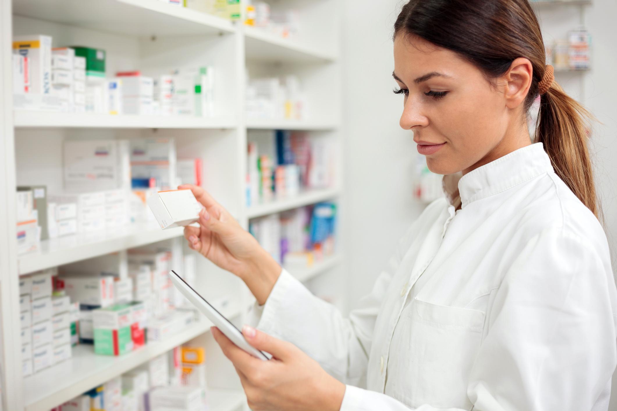 Female pharmacist takes drugs off a shelf