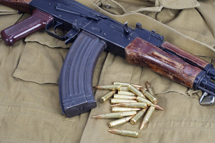 AK-47 and bullets laying on top of a khaki uniform
