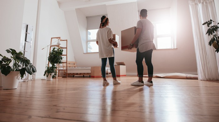 Two people carrying boxes into a mostly empty room in a house