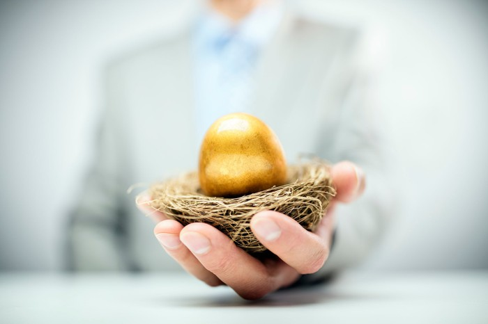 A man in a suit holding out a nest with a golden egg sitting in it