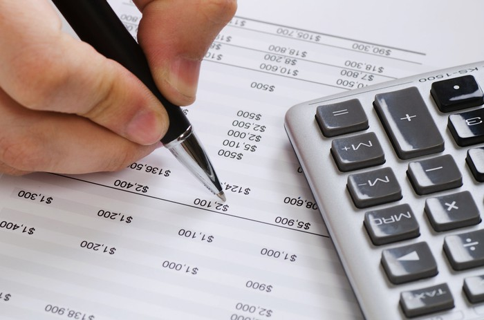 A close-up of someone marking a balance sheet with a pen, and a calculator nearby