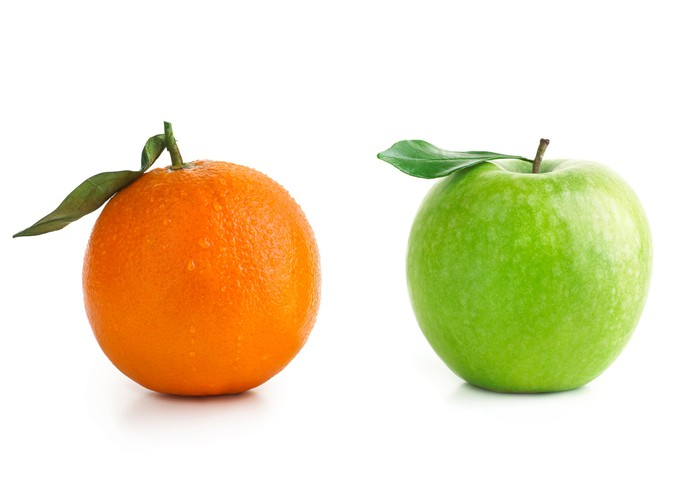 An orange and a green apple compared side by side.