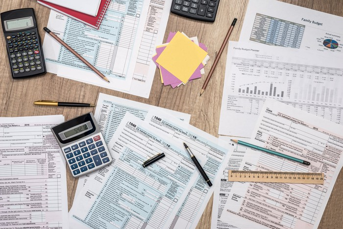 Various tax forms on top of a wooden table, with calculators, pens, a ruler, and Post-its strewn around them.