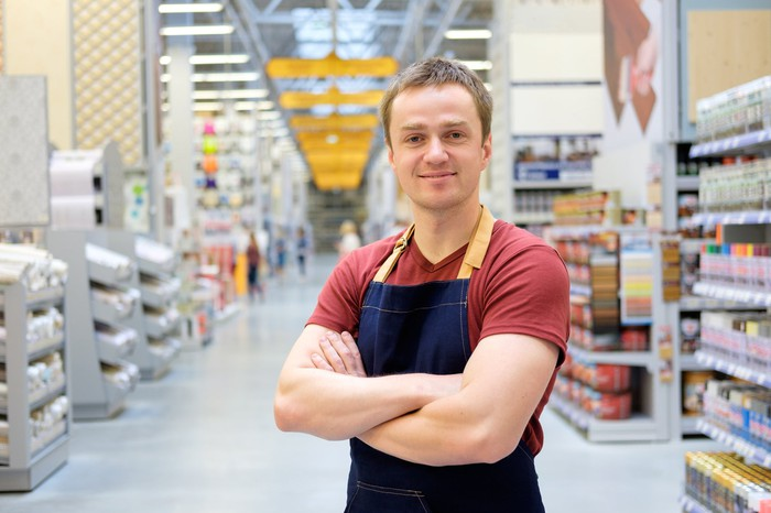 An aproned employee stands in the aisle of a warehouse store.