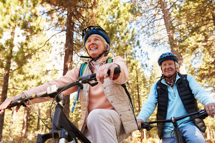 An older couple riding bikes in the woods.