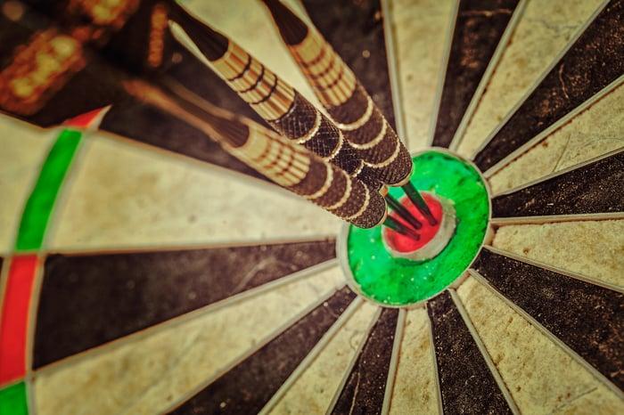 three darts in a dart board's bulls eye.
