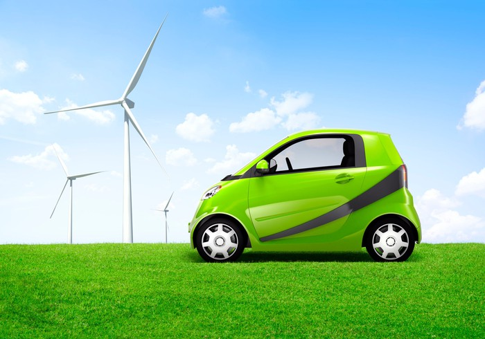 A compact green electric car in a field with windmills in the background.