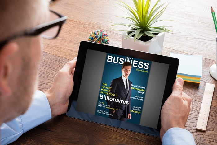 Man looking at tablet with Business magazine showing a story on billionaires.