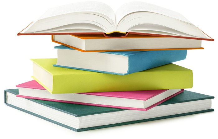 A stack of several books with one open on top.