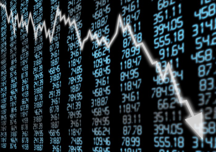 A downward-trending arrow superimposed over a stock ticker board.