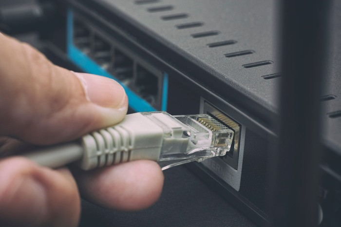 Hand plugging cable into modem
