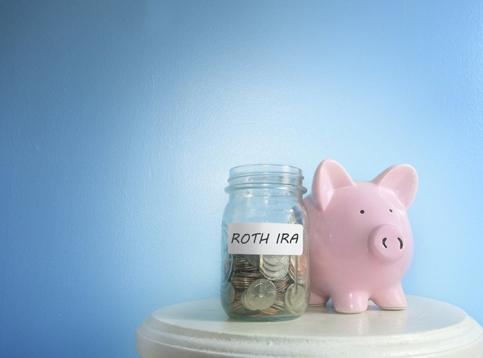 A jar with the label ROTH IRA filled with coins next to a pink piggy bank on a little round table.