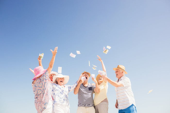 Senior citizens dressed for vacation, happily throwing cash into the air against a blue sky.