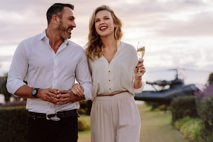 Elegant, wealthy couple walks outside holding glasses of champagne