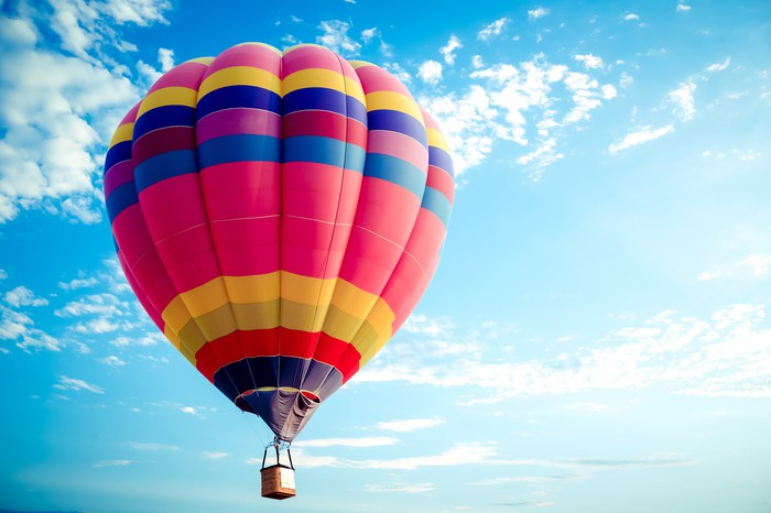 A colorful hot air balloon soars into the sky.