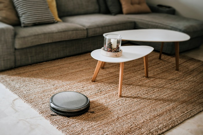 A robotic vacuum working on the floor in a living room