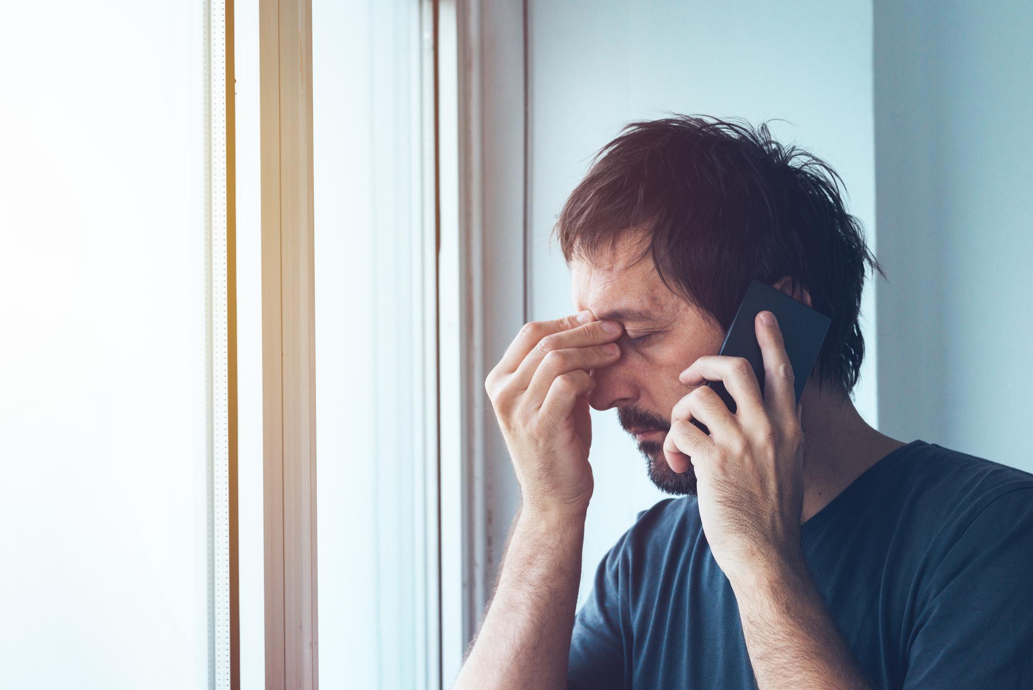 Man on telephone, pinching bridge of nose in frustration