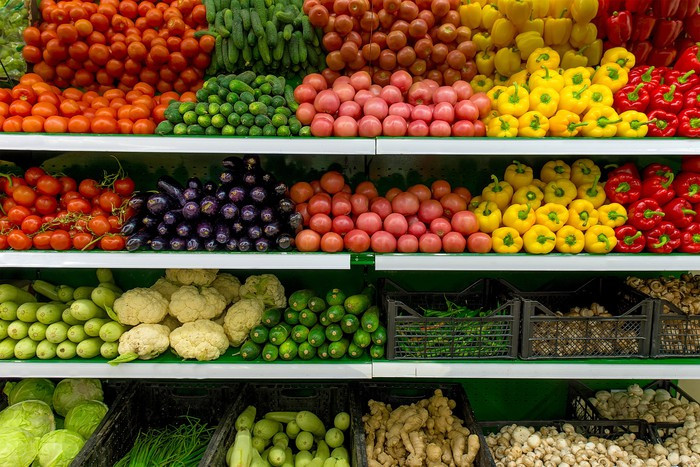 Shelves of vegetables in a supermarket, including peppers, tomatoes, eggplants, cauliflower, ginger, and more