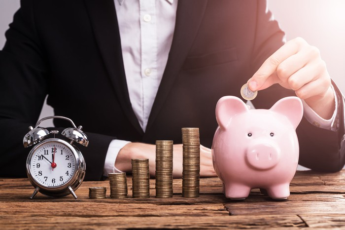 With an alarm clock and growing stacks of coins in front of him, a man drops a coin into a piggy bank.