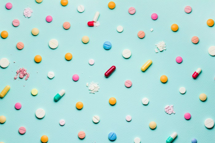 Many different pills and capsules on a blue background, with some of the pills crushed