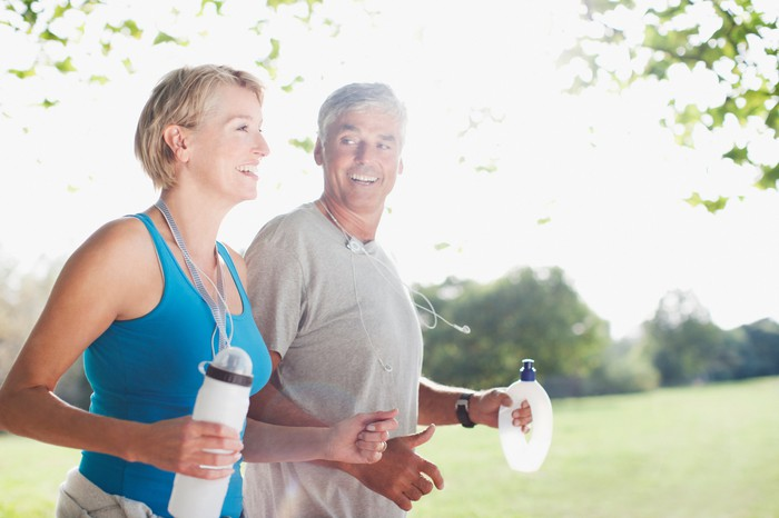 Fifty-plus year old couple, jogging, holding water bottles.