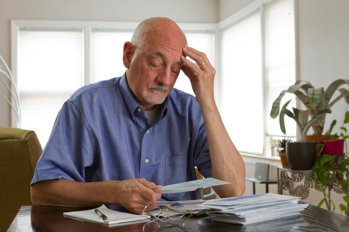 Senior man looking at a stack of bills, appearing worried.