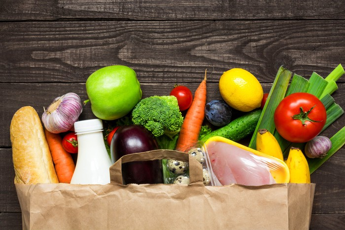 A paper grocery bag full of fresh produce.