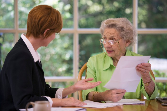 Senior woman holding piece of paper and listening to financial planner at a table