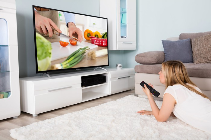 Woman watching cooking show on TV