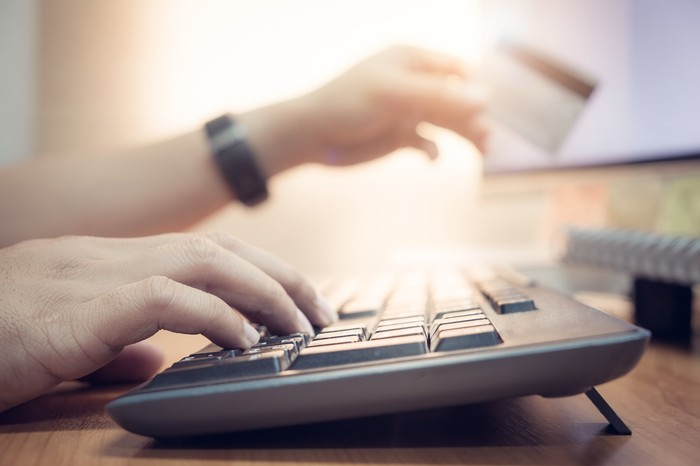 Hand typing on a keyboard with the other hand holding a credit card.