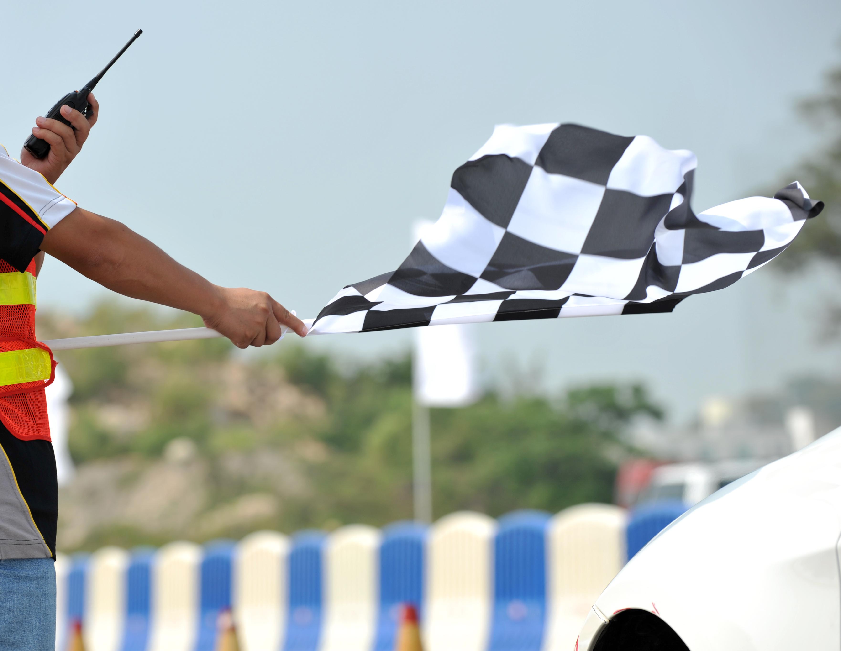 Checkered flag waving at a car race.