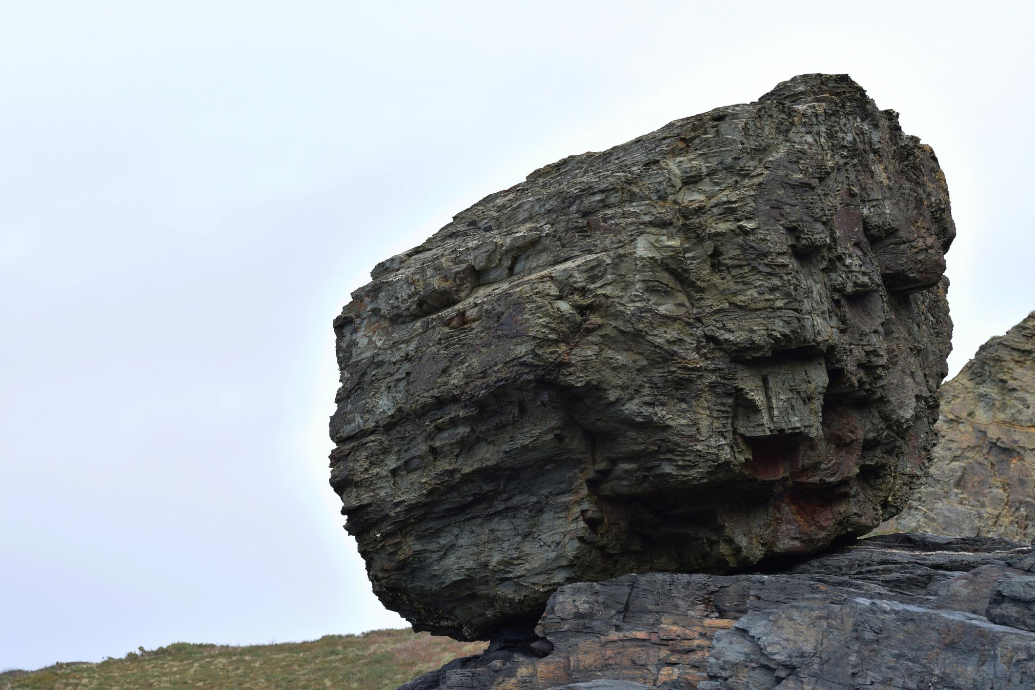 A large rock on a hillside.