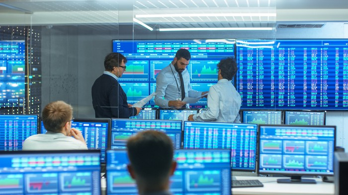 Several stock traders discuss business while surrounded by screens displaying market data.