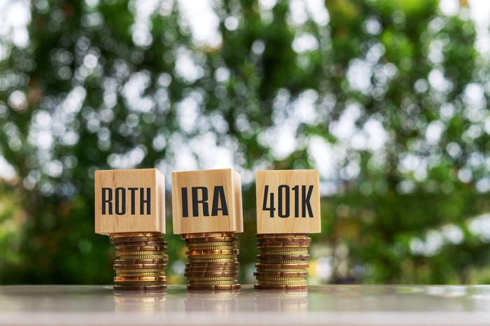 "Blocks that say ""Roth,"" ""IRA,"" and ""401K"" on top of stacks of coins."