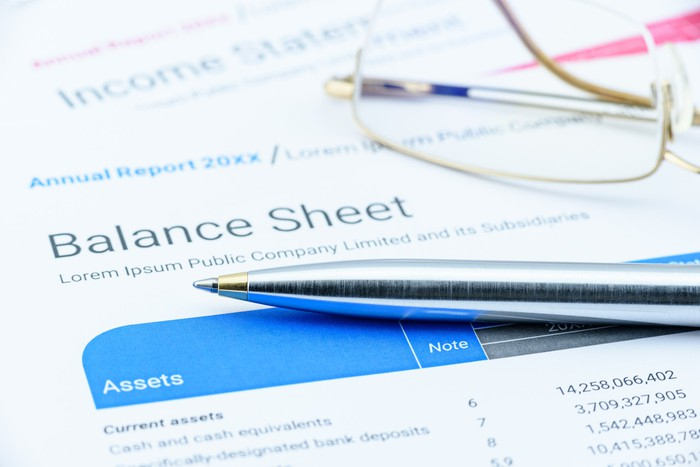 A balance sheet with eyeglasses and a pen lying on it.