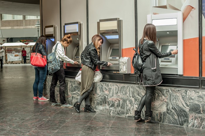 Several women use a row of ATMs.